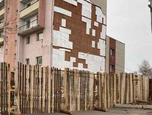 В центре Биробиджана обнесли забором дом, у которого отвалилась облицовка